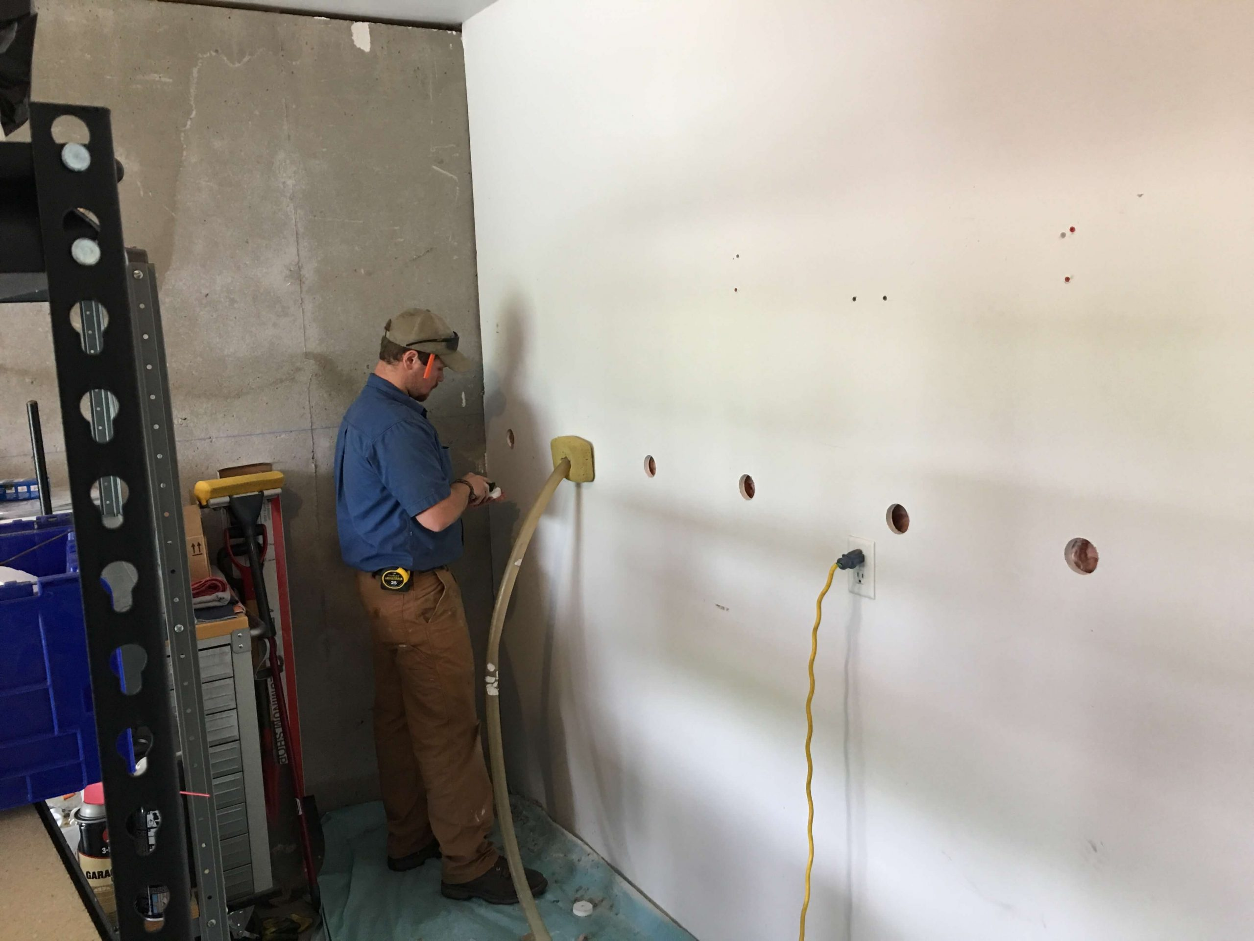man drilling holes on the wall