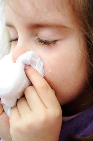 Sick little girl with tissue and tears